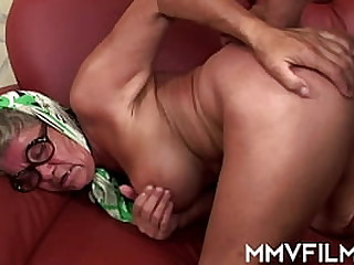 Chesty granny in glasses teasing with her sexy big tits and taking a big young schlong on her knees